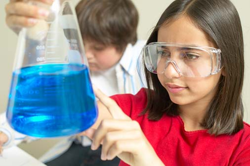 elementary school students in science lab with beaker